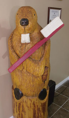 Wooden carving of beaver with large white front teeth and a toothbrush
